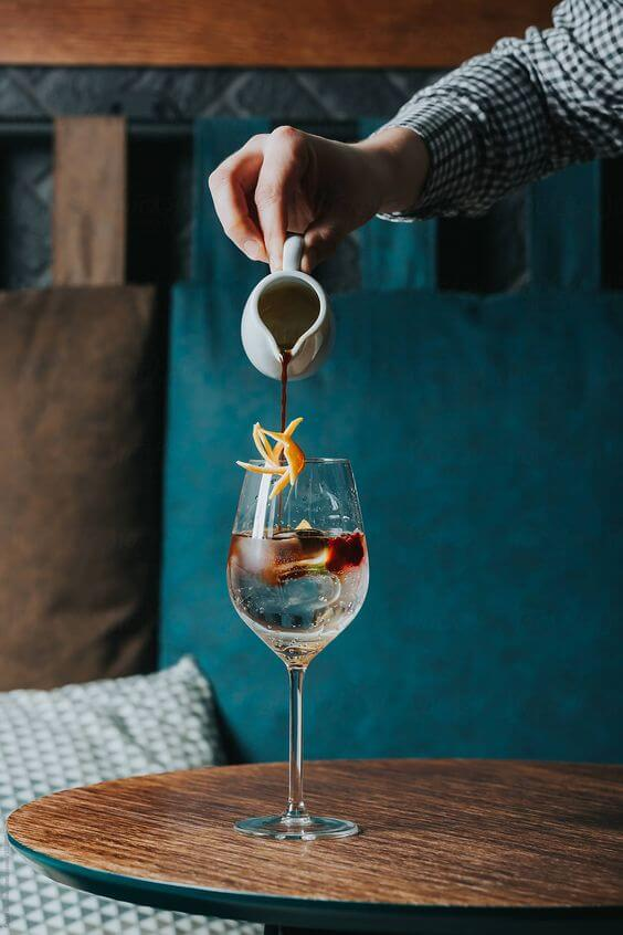 Cocktail being served in tall glass on wooden table