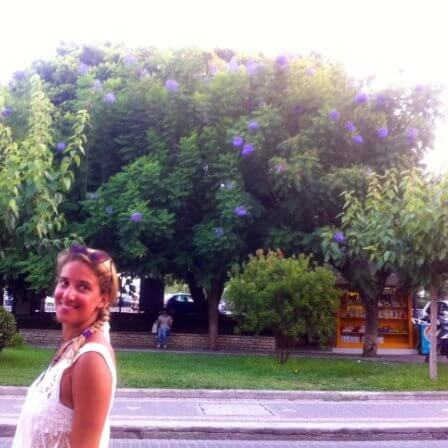 Woman next to road with trees